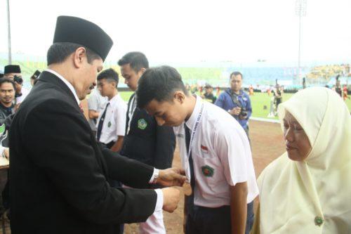 Dr H Mustain SAg Kepala Kemenag Kabupaten Malang Serahkan Piagam Penghargaan Kepada M Rofiqul Huda Juara KSM Nasional. (H Mansyur Usman/Memontum.Com)
