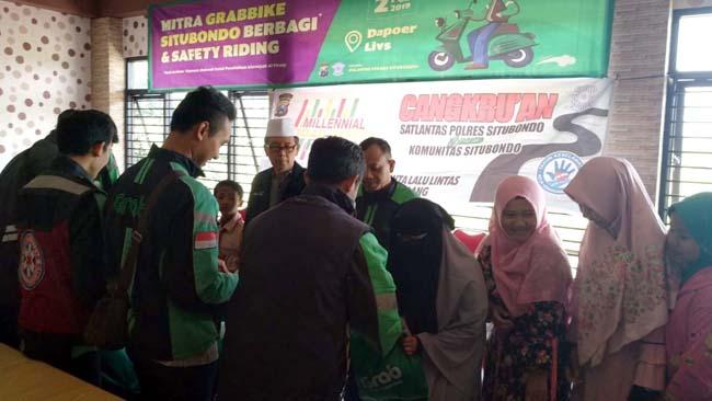 BERIKAN SANTUNAN: Driver mitra GrabBike Situbondo menyerahkan bantuan pada anak yatim Al-Firosy Cabang Situbondo. (im)