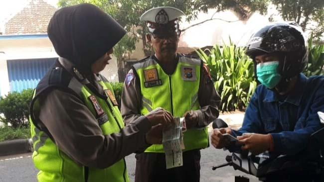 Petugas Polsek Tanggulangin, saat memeriksa surat-surat kendaraan, STNK dan SIM pada pengendara motor (gus)