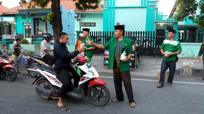 BERIKAN TA'JIL: Ketua PAC Ansor Situbondo kota, Joko Supratikno tampak memberikan ta'jil pada pengendara sepeda motor. (im)