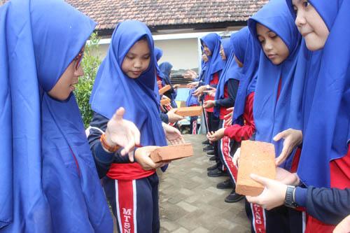 Para siswa-siswi MTsN 1 bergotong-royong memindahkan batu bata secara marathon ke area pembangunan ruang kelas. (rhd)