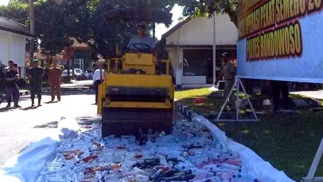 DIHANCURKAN: Polres Bondowoso menghancurkan 800 lebih botol miras oplosan dengan mesin penggilas. (guido)