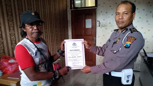 TERIMA PIAGAM: Drs Mohd Yusuf Millenial mantan Jurnalis asal Riau saat menerima penghargaan di Mapolres Situbondo, kemarin. (im)