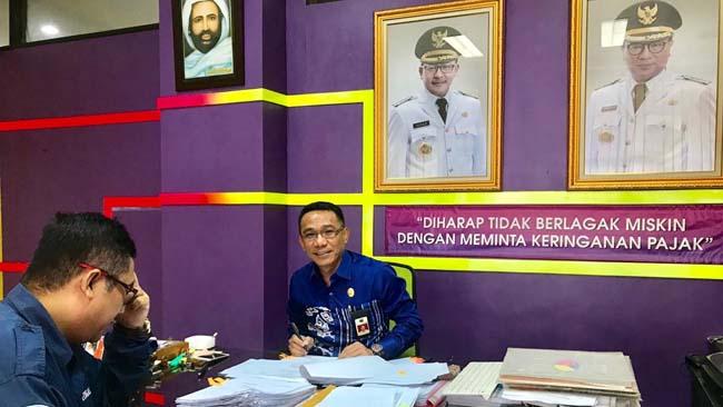 Kepala BP2D Kota Malang, Ir H Ade Herawanto MT dengan setumpuk berkas pengajuan keringanan pajak di meja kerjanya. (ist/humas)