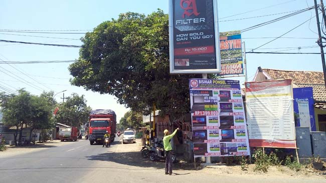 Baliho raksasa dikeluhkan masyarakat dan pengguna jalan di pertigaan jalan raya Desa Wringin Anom, Kecamatan Panarukan. (im)