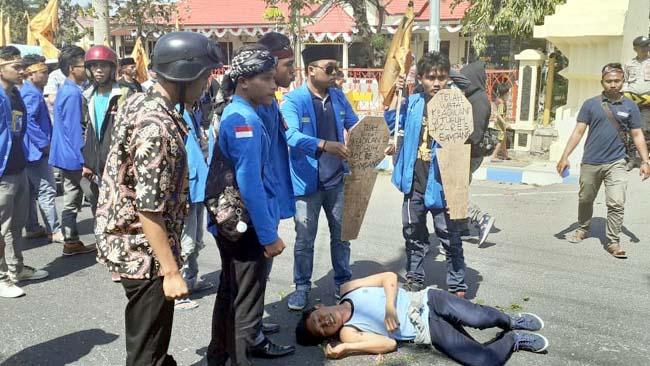 Massa saat melakukan teatrikal di depan Mapolres Sampang. (zyn)