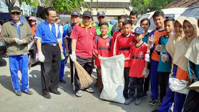 GOTONG ROYONG : Sekretaris Daerah Kabupaten Sampang Yuliadi Setiawan saat bersih-bersih di Pasar Srimangunan bersama para siswa dalam acara World Clean Up Day. (zyn)
