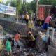 Petugas dari DLHK Kabupaten Sidoarjo sedang membersihkan sampah menumpuk pada Avfur Sidomukti di sekitar perempatan jalan Wonoayu. (par)