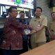 Sekda Kota Malang saat memberikan buku 50 inovasi Bapenda Kota Malang kepada perwakilan dari Pemkab Bangkalan. (gie)