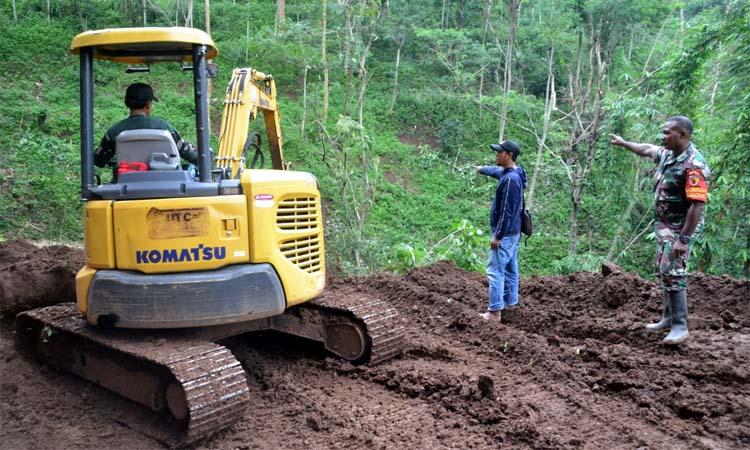 TURUNKAN ALAT BERAT: Anggota Kodim 0823 / Situbondo bekerja keras membangun jalan di lokasi Pra TMMD ke 107 di Desa Tlogosari. (im)