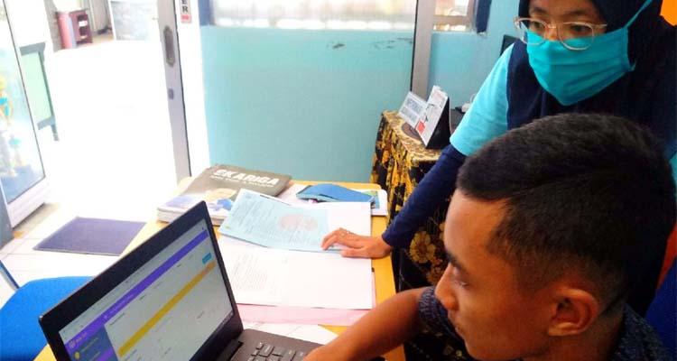 Petugas memandu salah satu calon siswa yang kesulitan input data secara online. (Adn)