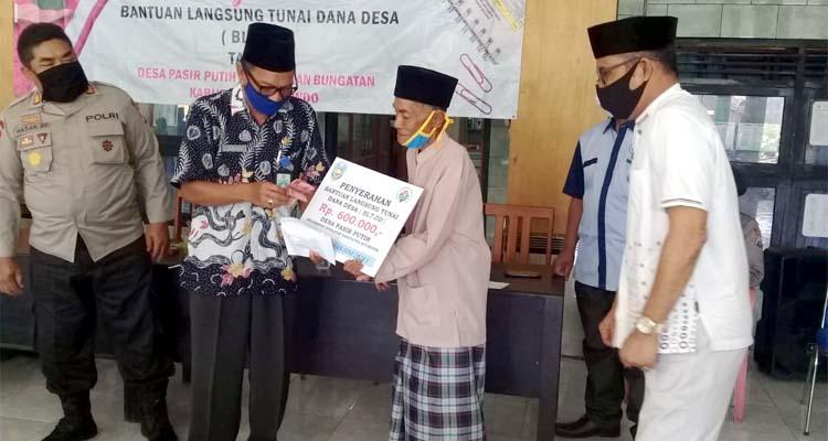 Kepala Desa Pasir Putih, H Zaenal bersama Camat Bungatan yang diwakili oleh Sekcam H Junaedi saat menyalurkan BLT-DD tahap III tahun anggaran 2020 secara simbolis. (her)