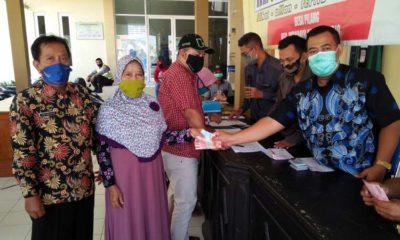 Arip Masjidin Sekretaris Desa Pilang mendampingi warganya menerima BLT DD. (par)