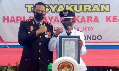 Ahmadi Kepala Desa Pesisir Besuki saat menerima penghargaan dari Kapolres Situbondo AKBP Sugandi SIK M Hum. (her)