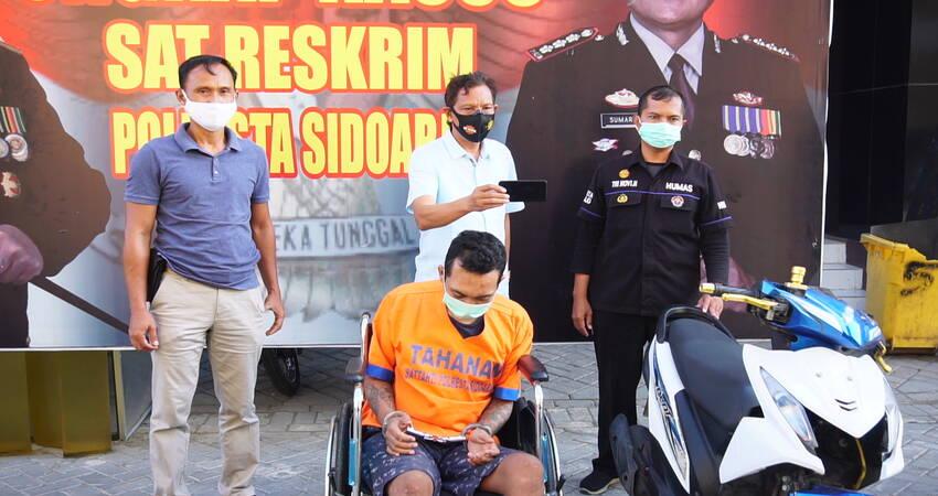 DITEMBAK: Kedua kaki tersangka perampasan motor, M Zaki Nurdin (24) warga Mojokerto ditembak kakinya dipamerkan bersama barang bukti motor Honda Beat rampasannya di Polresta Sidoarjo, Selasa (13/10/2020) sore.