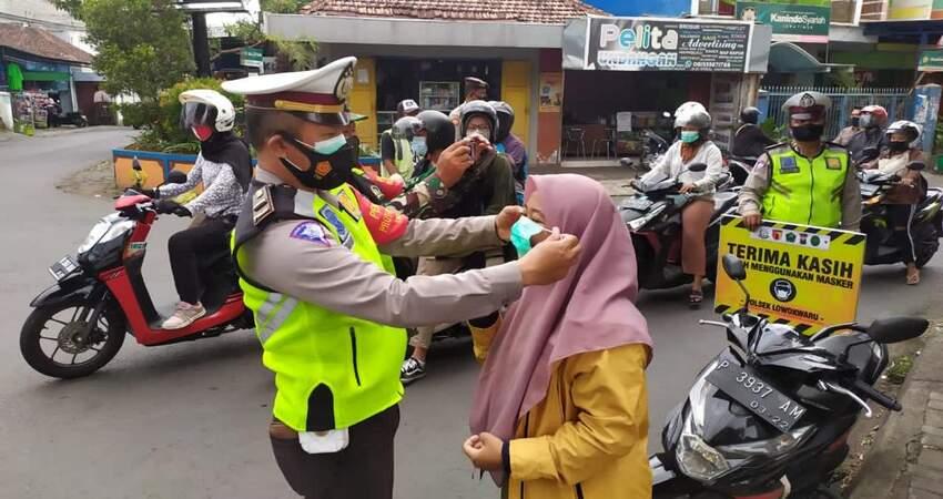Petugas memasangkan masker kepada ibu-ibu yang ditemui di jalan. (ist)