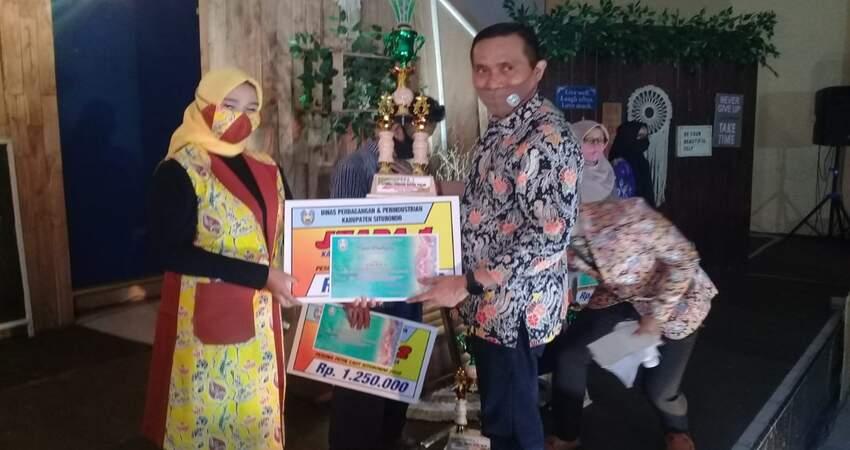 Kepala Dinas Perdagangan dan Perindustrian Kabupaten Situbondo Abdul Kadir Jaelani S Sos M Si saat memberikan hadiah kepada Juara 1 lomba kegiatan Batik Situbondo New Normal Fashion. (her)