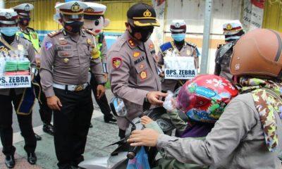 Kapolres Lumajang, AKBP Deddy Foury Millewa bersama anggota Satlantas membagi-bagikan kelengkapan standar protokol kesehatan (Prokes).