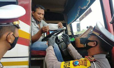 Kasat Lantas Polresta Malang Kota AKP Ramadhan Nasution SH SIK saat membagikan masker ke sopir bus. (ist)