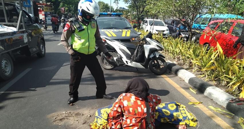 EVAKUASI: Petugas mengevakuasi jenazah, Ny Hartik (54) warga Keputran Pasar Kecil, Kecamatan Tegalsari, Surabaya yang tewas terlindas truk di JL Raya Desa/Kecamatan Buduran, Sidoarjo, Senin (12/10/2020).