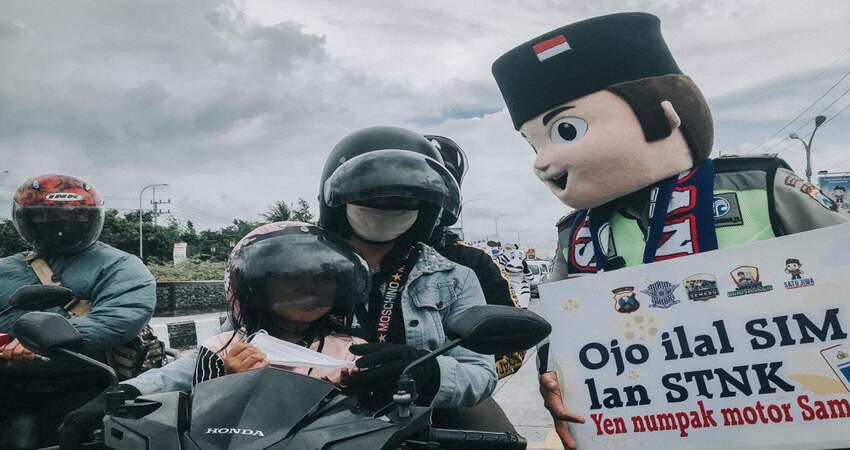 Maskot Satlantas Polres Malang ingatkan pengendara untuk taat berlalu lintas.