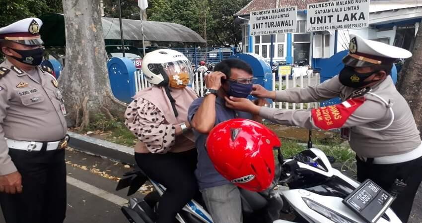 Kasubnit I Laka Lantas Polresta Malang Kota Ipda Deddy saat memakaikan masker kepada pengguna kendaraan . (gie)