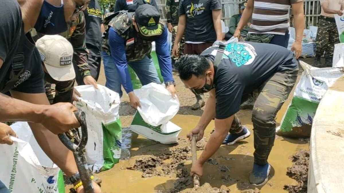 Ratusan Gerakan Pemuda Ansor Kraksaan Bersihkan Lumpur Sisa Banjir Dringu Probolinggo